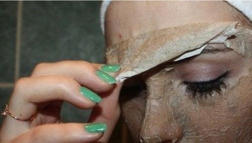 Mulher tirando a máscara de ovo