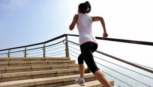 Mulher subindo escadas correndo fazendo esforço nos joelhos