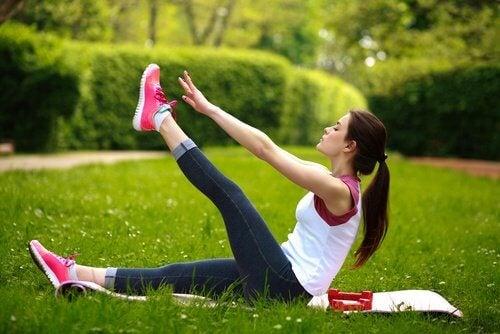 Mulher fazendo levantamento de pernas para fortalecer a parte inferior das costas