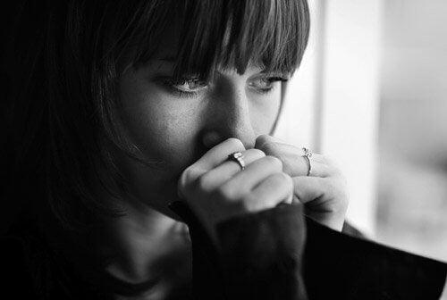 Moça com depressão olhando pela janela