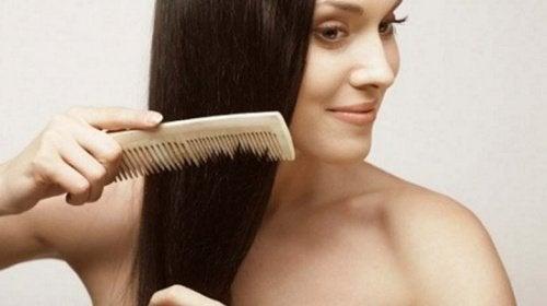 Mulher penteando o cabelo para evitar sua queda