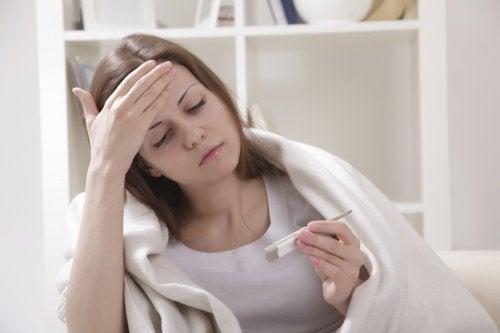 Mulher medindo a febre com termômetro