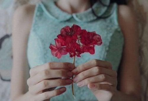 mulher-com-flor-vermelha-representando-felicidade