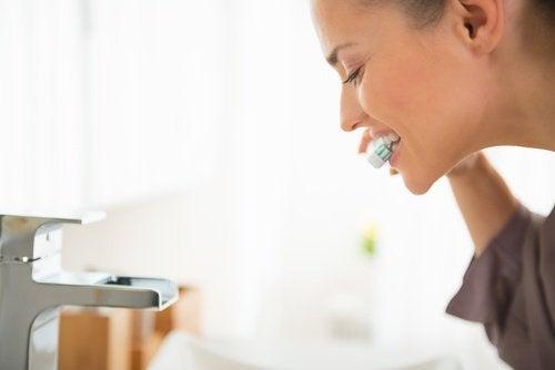 Mulher branqueando os dentes com água oxigenada