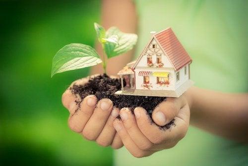 Mulher segurando uma casa na mão