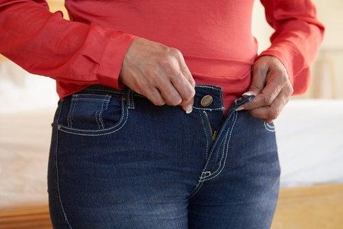 Mulher tentando abotoar calças apertadas