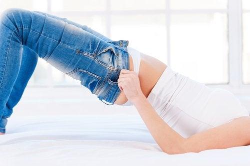 Mulher colocando calças apertadas