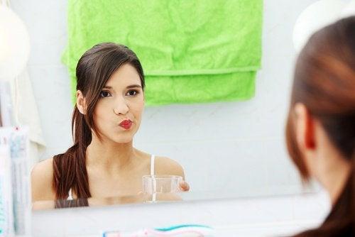 Mulher fazendo gargarejos de sal e água para aliviar a dor de garganta