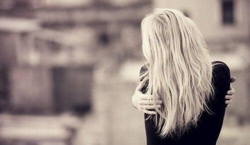 Mulher se abraçando e dando autopiedade