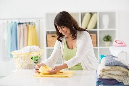 Mulher dobrando roupa e lidando com a depressão