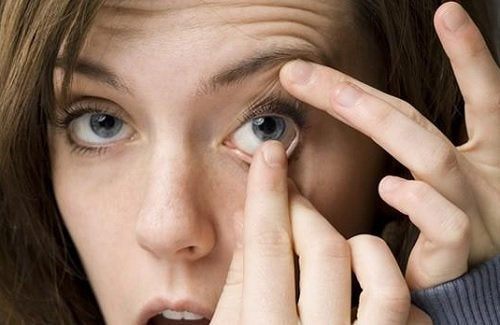 Mulher tocando os olhos com as mãos