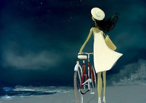Mulher com bicicleta na praia
