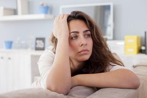 Mulher magoada pensando se deve iniciar um novo relacionamento