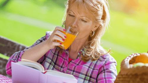 Mulher bebendo Remédio com cenoura e alho para combater o esgotamento