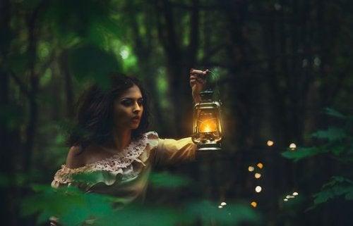 mulher-em-floresta-com-lamparina