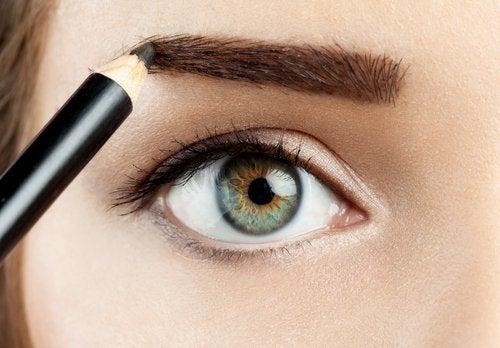 Mulher pintando sobrancelhas escassas