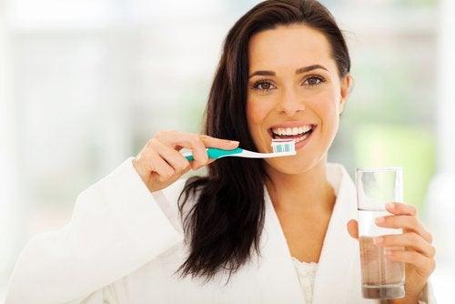 Mulher escovando os dentes com a mão não util para evitar Alzheimer