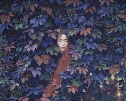 Mulher escondida entre plantas e que sente baixa autoestima