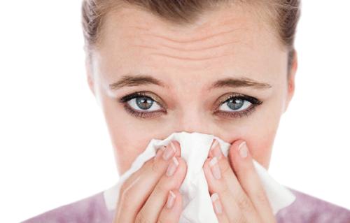 Mulher com rinite alérgica espirrando
