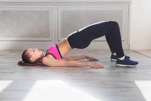 Mulher fazendo exercícios de ponte para melhorar a digestão