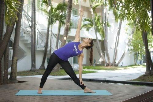 Mulher fazendo exercícios de triángulo para melhorar a digestão