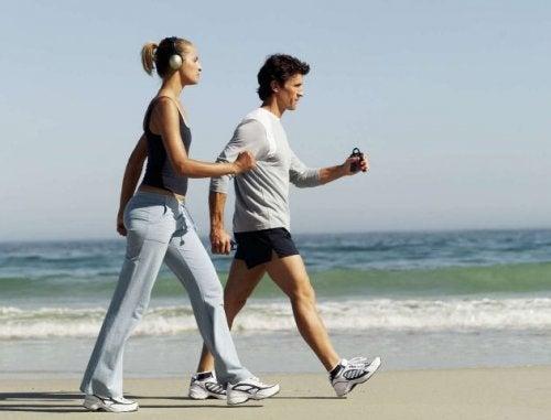 Casal andando na praia para perder peso