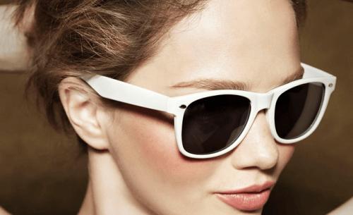 Mulher protegendo os olhos com óculos de sol