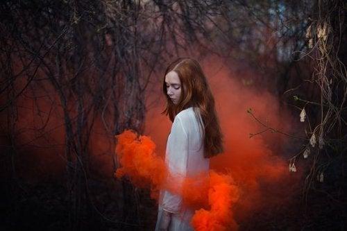 Mulher rodeada de fumaça vermelha