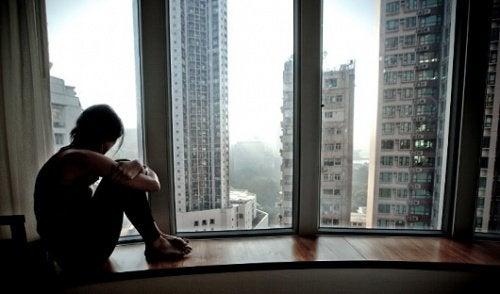 Mulher olhando pela janela e pensando com a mente