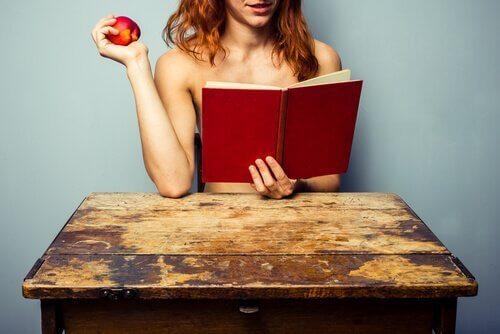 mulher_nua_lendo_livro_mesa_com_maca