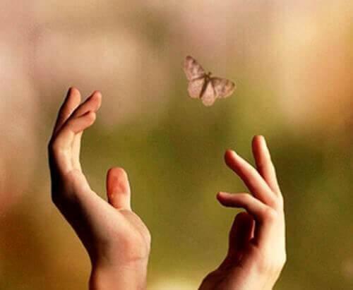 mãos deixando ir assuntos pendentes em forma de borboleta