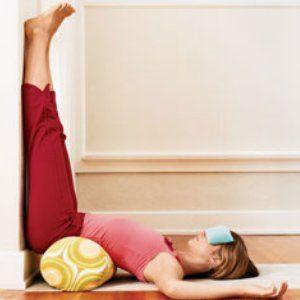 Mulher se alongando com as pernas para cima para eliminar o estresse