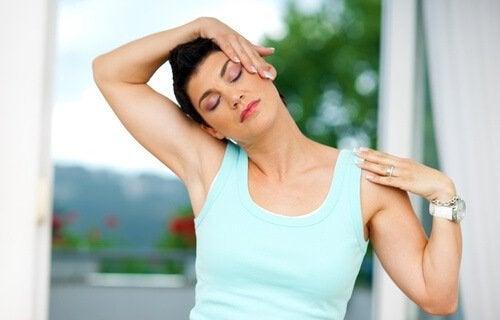 Mulher aliviando a dor no pescoço através de alongamentos