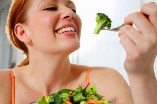 Mulher comendo brócolis