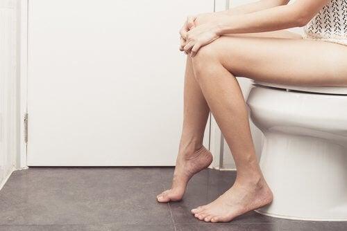 Pessoa com hemorroidas no banheiro
