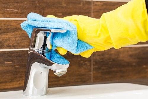 Mulher passando pano para limpar a torneira