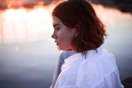 Mulher triste observando o reflexo do lago