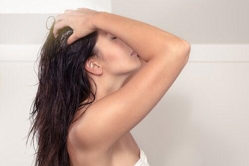 Mulher lavando o cabelo com vinagre de cidra de maçã
