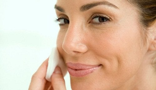 Mulher passando vinagre de cidra de maçã no rosto