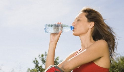 Mulher bebendo água para desintoxicar o organismo