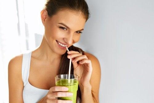 Mulher tomando suco para combater o envelhecimento precoce