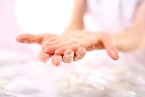 Pessoa esfregando as mãos com esfoliante