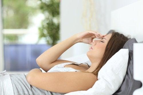 Mulher cansada e com dor de cabeça