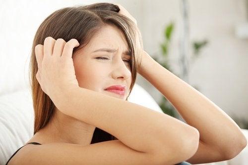 Moça com dor de cabeça por causa do hipotireoidismo
