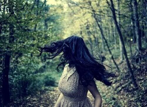 Mulher correndo com medo no bosque
