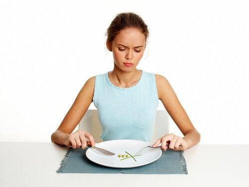 Mulher com o hàbito matinal de comer em exesso