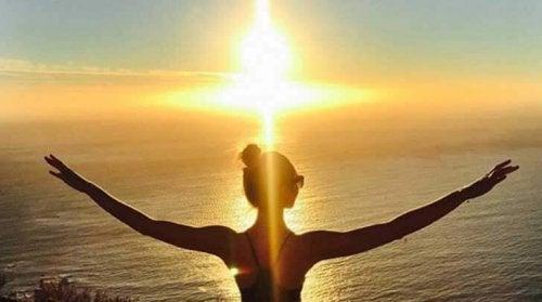 Mulher olhando o caminho do sol