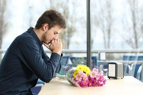 Homem depressivo com ramilhete de flores