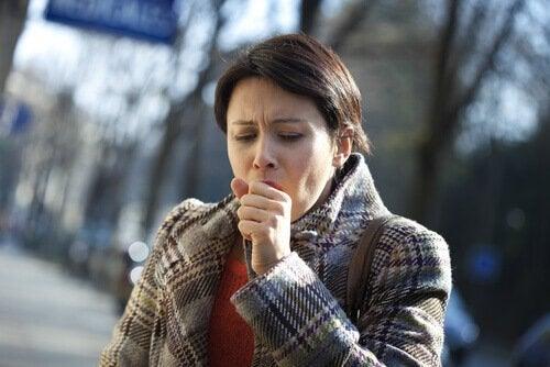 Mulher tossindo por causa do câncer de pulmão