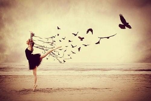 Mulher com pássaros em praia vazia